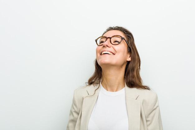 Jonge europese onderneemster ontspannen en gelukkig lachen, nek gestrekt met tanden.