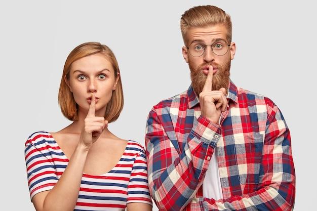 Jonge europese vriend en vriendin, stilte teken tonen, kijkt met verbaasde uitdrukkingen, toon stil gebaar