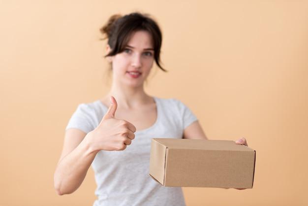 Jonge europese vrouw adverteert kartonnen doos op de voorgrond, gebaren naar de kwaliteit met haar vinger omhoog, reclame-concept