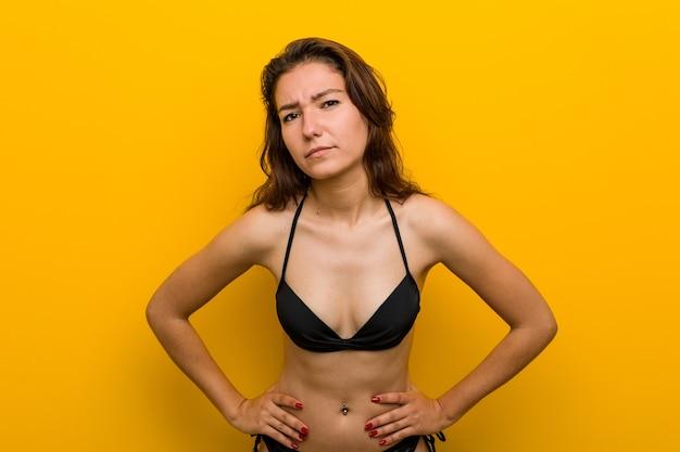 Jonge europese vrouw die bikini draagt die zeer boos iemand uitscheldt.