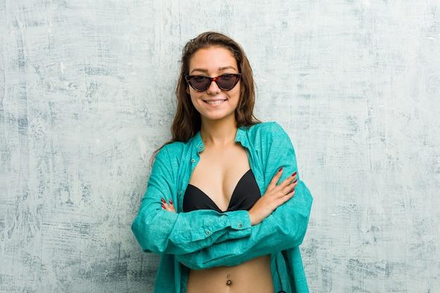 Jonge europese vrouw die bikini draagt die zelfverzekerd met gekruiste armen glimlacht.