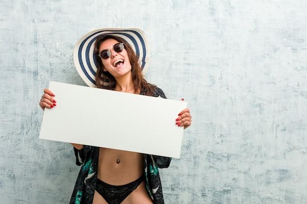 Jonge europese vrouw die bikini draagt en een aanplakbiljet houdt