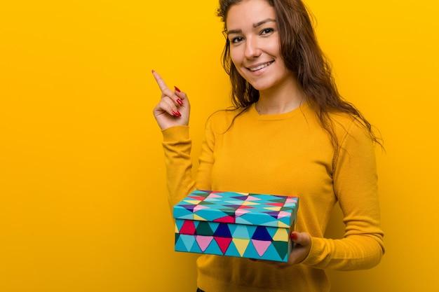 Jonge europese vrouw die een gift houdt glimlachend vrolijk wijzend met weg wijsvinger.