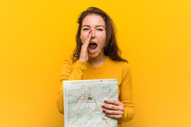 Jonge europese vrouw die een kaart houdt die opgewonden aan voorzijde schreeuwt.