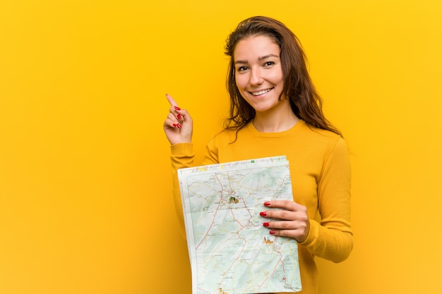 Jonge europese vrouw die een kaart houdt glimlachend vrolijk wijzend met weg wijsvinger