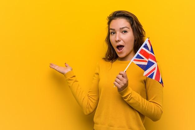 Jonge europese vrouw die een vlag houden van het verenigd koninkrijk onder de indruk van het exemplaar op palm.