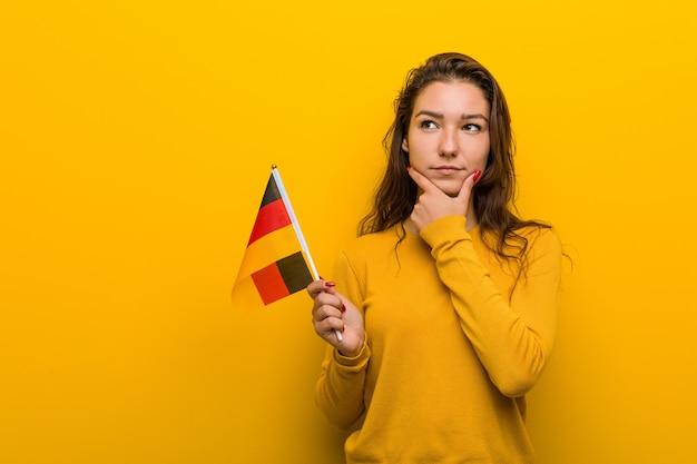 Jonge europese vrouw die een vlag van duitsland houdt die zijwaarts kijkt met een twijfelachtige en sceptische uitdrukking.