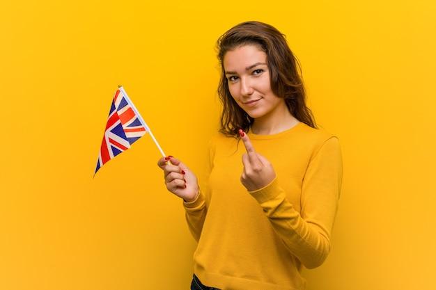 Jonge europese vrouw die een vlag van het verenigd koninkrijk houdt die met de vinger naar je wijst alsof ze dichterbij komt.