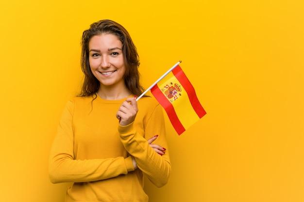 Jonge europese vrouw die het spaanse vlag glimlachen houden zeker met gekruiste wapens.