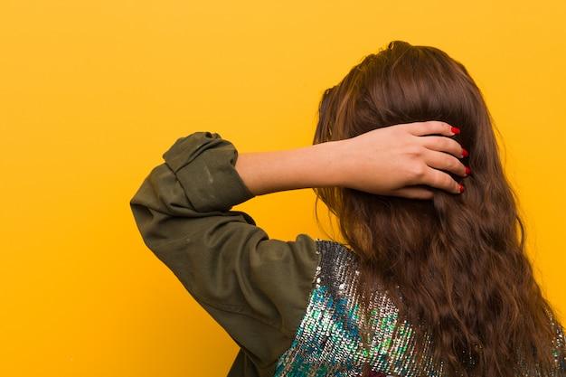Jonge europese vrouw die over gele achtergrond van achter wordt geïsoleerd die over iets denkt.