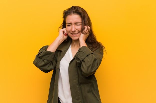 Jonge europese vrouw die over gele achtergrond wordt geïsoleerd die haar oren behandelt met haar handen
