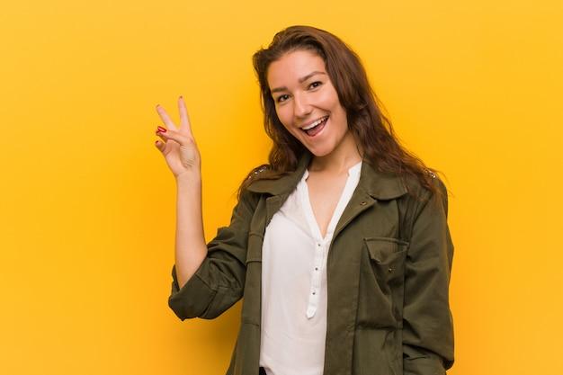 Jonge europese vrouw die over gele blij en onbezorgd het tonen van een vredessymbool met vingers wordt geïsoleerd.