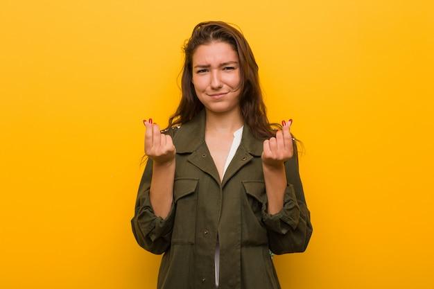 Jonge europese vrouw die over gele muur wordt geïsoleerdr die aantoont dat zij geen geld heeft.