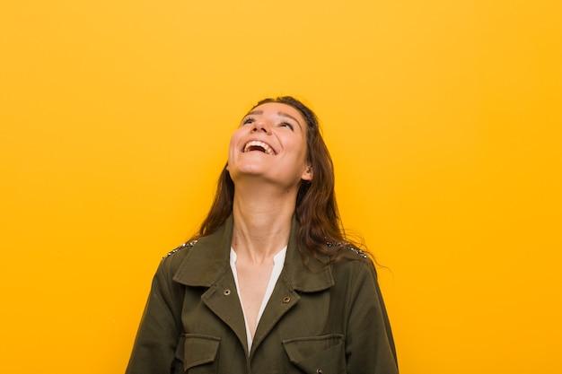 Jonge europese vrouw geïsoleerd over gele muur ontspannen en gelukkig lachen, nek uitgerekt met tanden.