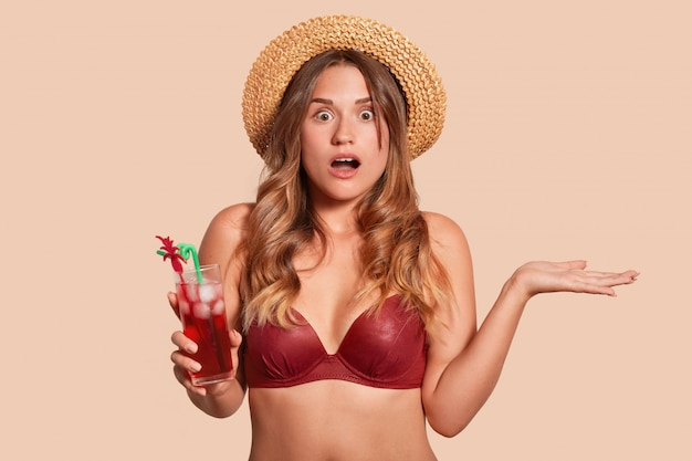 Jonge europese vrouw, gekleed in rood zwempak en strohoed wordt geschokt als gevolg van dreigend gevaar, met een glas verse, smakelijke cocktail, poseren met open mond en wijd open ogen, drukt verbazing uit.