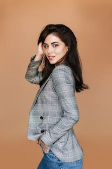 Jonge europese vrouw in jeans en geruite jas vormt voor portret op beige muur.