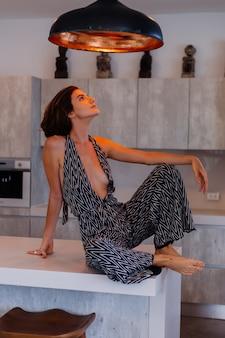Jonge europese vrouw in jumpsuit zit op de keukentafel onder het oranje warme licht van het plafond