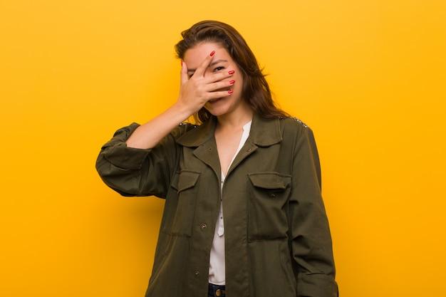 Jonge europese vrouw knippert met haar vingers, beschaamd over haar gezicht.
