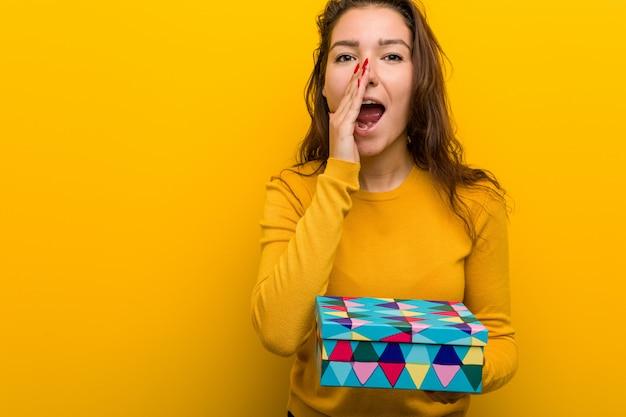 Jonge europese vrouw met een geschenk schreeuwen opgewonden aan de voorkant.