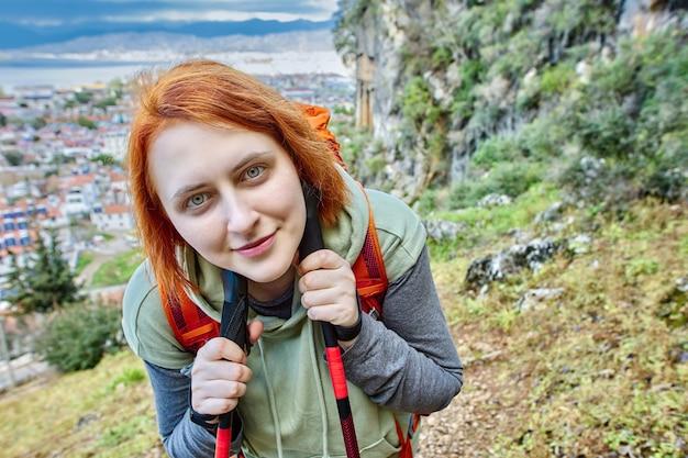 Jonge europese vrouw met wandelstokken tegen achtergrond van lycisch graf.