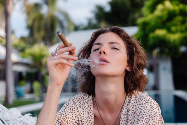 Jonge europese vrouw rookvrije sigaar liggend op een hangmat buiten tropische luxevilla hotel, zonsondergang natuurlijk licht