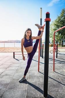 Jonge europese vrouwelijke atleet die aan muurstaven hangen die touw buiten doen. sport actieve levensstijl concept.