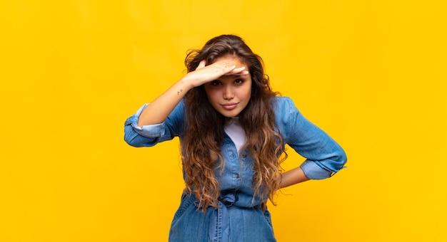 Jonge expressieve vrouw die zich voordeed op gele muur