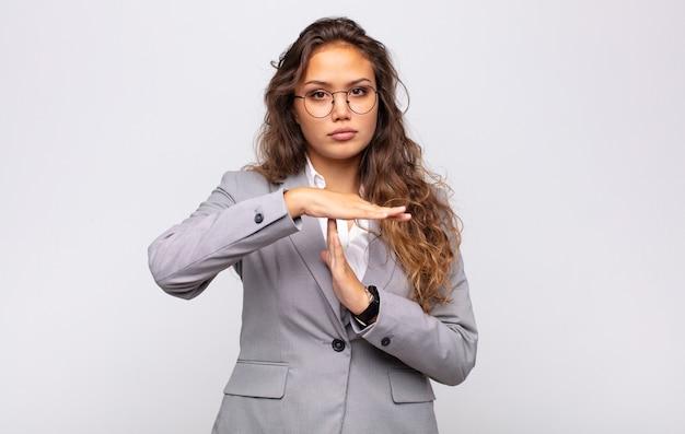 Jonge expressieve vrouw met bril en elegant pak poseren op witte muur