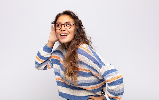 Jonge expressieve vrouw met een bril die zich voordeed op een witte muur