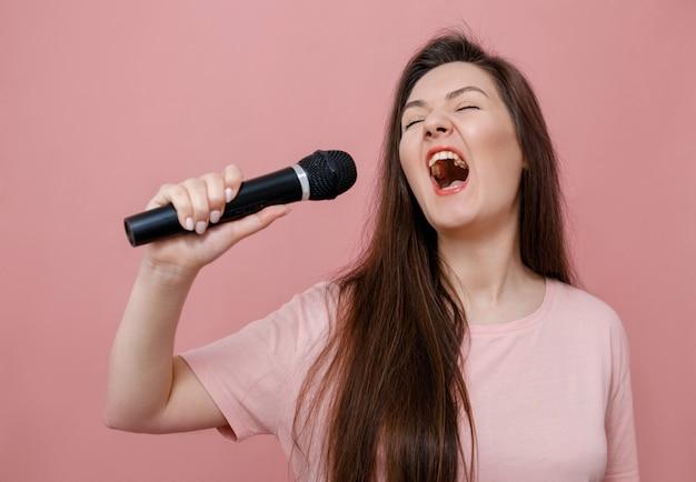 Jonge expressieve vrouw met microfoon in hand op roze achtergrond