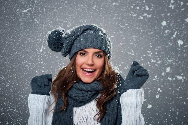 Jonge extatische vrouw geniet van eerste sneeuw