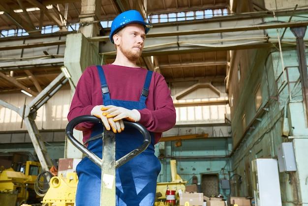 Jonge fabrieksarbeider bij ruime magazijn