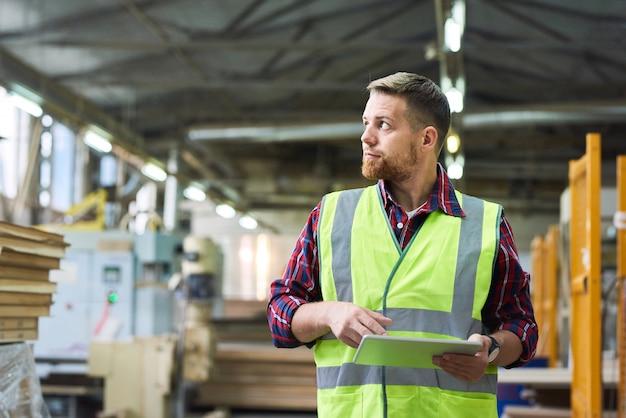 Jonge fabrieksarbeider die digitale tablet gebruiken