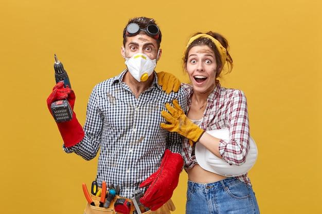 Jonge fabrieksarbeiders kijken met afgeluisterde ogen terwijl ze tegen een gele blinde muur staan. knappe professionele dakdekker in beschermend masker met elektrische boor met kit van instrumenten