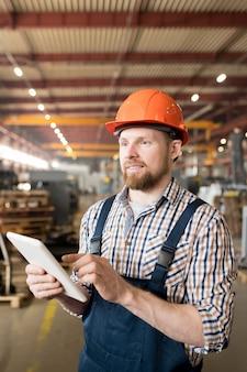 Jonge fabriekstechnicus die door online gegevens in touchpad scrolt terwijl hij het werkproces controleert