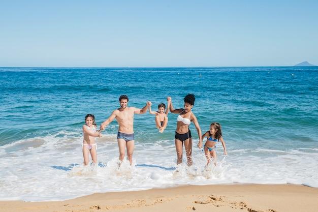 Jonge familie aan de kustlijn