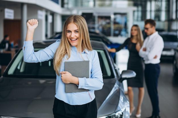 Jonge familie die een auto in een autotoonzaal kiest