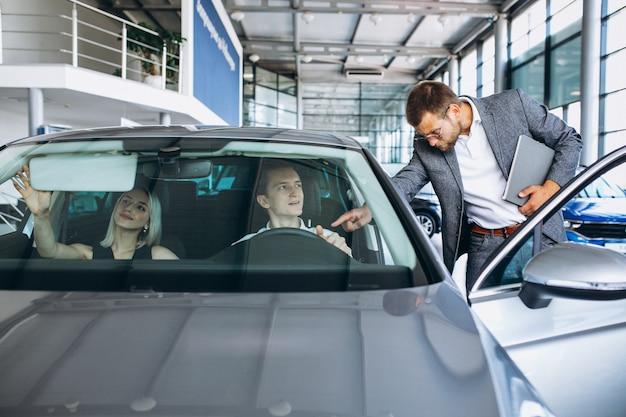 Jonge familie die een auto in een autotoonzaal koopt