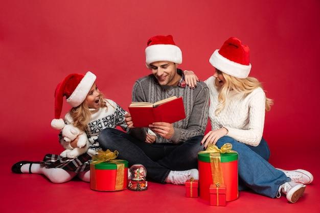 Jonge familie die kerstmishoeden geïsoleerd zitten dragen