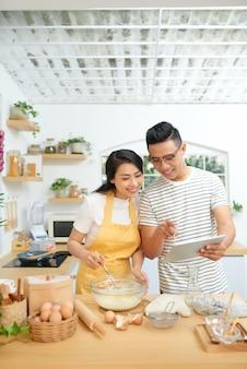 Jonge familie koken thuis, met behulp van digitale tablet. mockup voor recept