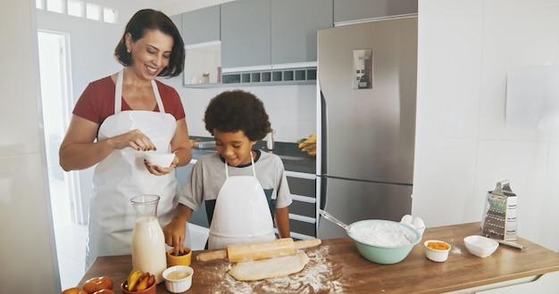 Jonge familie koken voedsel in de keuken. gelukkig klein meisje met haar moeder beslag mengen. moeder en kleine jongen bereiden het deeg voor. gelukkige familie in de keuken en junior chef-kok concept.