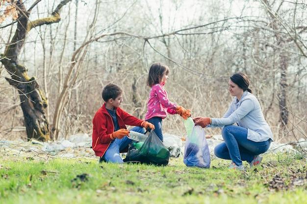 Jonge familie moeder met twee kinderen vrijwilligers maken het lentepark schoon, verzamelen afval en plastic flessen