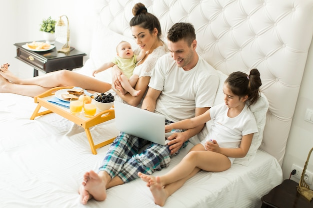 Jonge familie op het bed