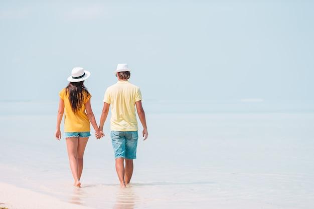 Jonge familie op wit strand tijdens zomervakantie.