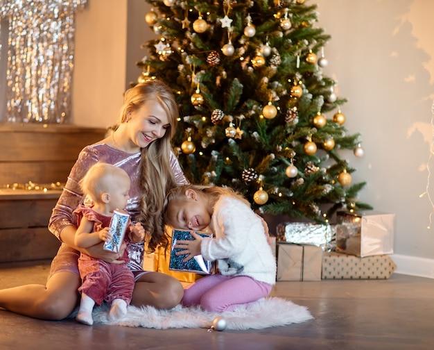 Jonge familiemoeder met lang blond haar met schattige dochters in de buurt van de kerstboom