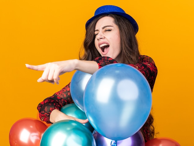 Jonge feestvrouw met een feesthoed die achter ballonnen staat en naar de zijkant wijst, schreeuwend met gesloten ogen geïsoleerd op een oranje muur