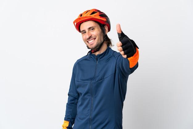 Jonge fietser man geïsoleerd op wit met duimen omhoog omdat er iets goeds is gebeurd