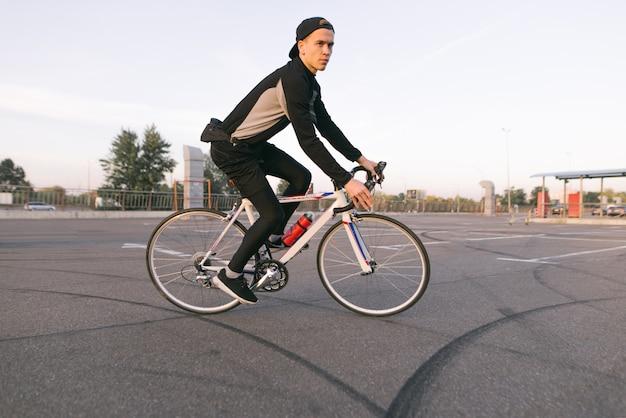 Jonge fietser rijdt op een parkeerplaats voor een fiets.