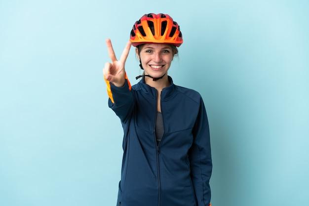Jonge fietser vrouw geïsoleerd op blauw glimlachend en overwinning teken tonen