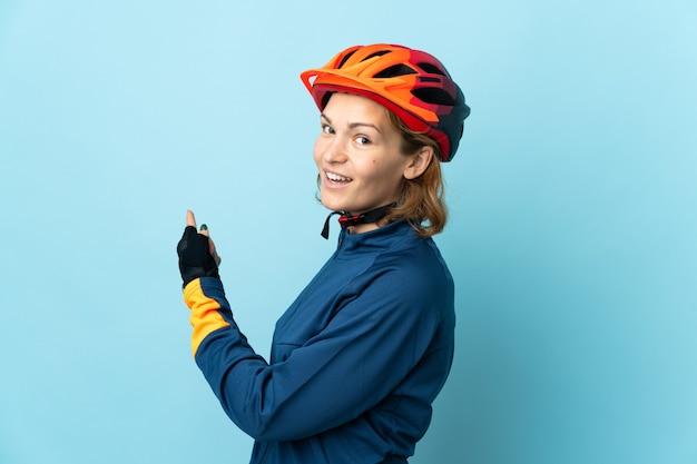 Jonge fietser vrouw geïsoleerd op blauwe achtergrond terug te wijzen